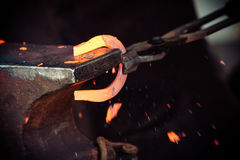 Hammering glowing steel - to strike while the iron is hot. Making decorative element in the smithy on the anvil. Hammering glowing steel. Blacksmith forges a Royalty Free Stock Images