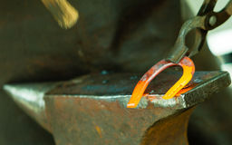 Hammering glowing steel - to strike while the iron is hot. Royalty Free Stock Photography