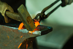 Hammering glowing steel - to strike while the iron is hot. Stock Photography