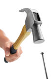 Hammering. Hand holding hammer hitting nail against white background Stock Photo