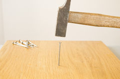 Hammering a nail into a board Stock Image