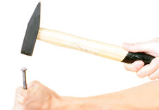 Hammering a nail into wooden plank. Royalty Free Stock Photo