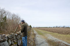 Hammering a pole. A farmer is hammering a pole in a rural landscape Stock Images