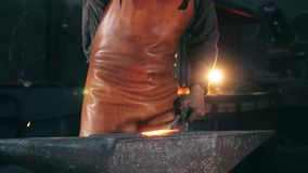 Hammersmith is beating inflamed metal in slow motion. Slow motion. Hammersmith is beating inflamed metal in slow motion. HD stock footage