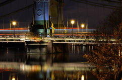 Hammersmith Bridge at night. Night shot of Hammersmith Bridge with reflections in the River Thames and the red lines of the London buses Stock Photos