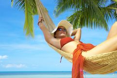 In hammock. View of nice woman lounging in hammock in tropical environment royalty free stock photos