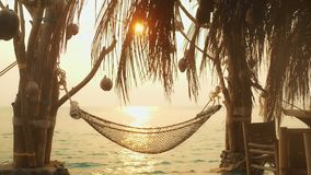 Hammock on beach hanging on palm tree for relaxing during summer vacation stock video footage