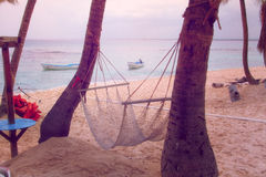 Relax, take it easy. Hammock hanging between palm trees on the beach Stock Photo