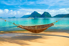 A Hammock at the Beach. A hammock at the Marimegmeg beach with the view of Bacuit Archipelago islands (El Nido, Philippines Stock Photo