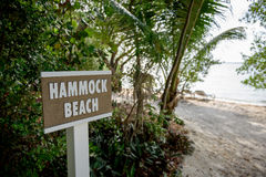 Hammock Beach sign. Sign post displaying the text Hammock Beach, set in a wooded area with a sandy beach and shoreline in the background Stock Photos
