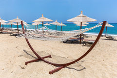 Hammock with beach umbrellas at coast Royalty Free Stock Photo