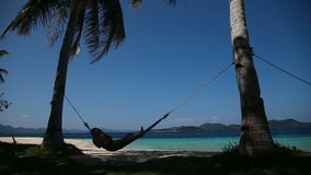 Hammock on beautiful beach. Silhouette of man in hammock on the beach.Idyllic beach with coconut trees and hammock.Travel concept stock video footage