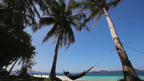 Hammock on beautiful beach. Silhouette of man in hammock on the beach.Idyllic beach with coconut trees and hammock.Travel concept stock footage