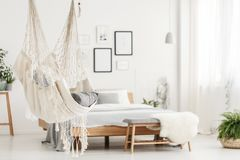 Hammock and bed in bedroom. Close-up of white hammock and blurred bedroom interior with wooden bed in the background Royalty Free Stock Photography