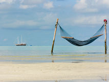 Hammock and boat. Photo of the hammock on the beach and ship in the sea on background Stock Photo