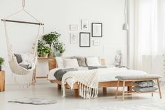 Hammock in bright bedroom. Grey fur rug under hammock in bright bedroom interior with bench, wooden bed and plants against wall with gallery royalty free stock photography