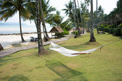 Hammock between coconut trees on tropical beach. Empty hammock between coconut trees on tropical beach Stock Photos
