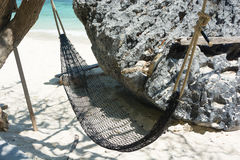 Hammock hanging with tree in shade at seaside sandy beach Stock Photography