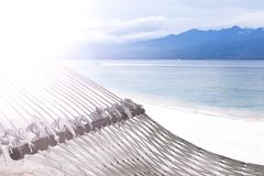Hammock on sandy beach on background of azure Bali Sea. Coast of the Gili Trawangan island, Indonesia. stock photos