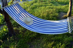 Hammock. Lazy summer holidays on hammock, rest with straw hat Stock Images