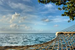 A hammock overlooking blue ocean and sky. stock photography