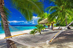 Hammock between palm trees on tropical beach of Rarotonga, Cook. Hammock between palm trees on a vibrant tropical beach of Rarotonga, Cook Islands, South Pacific Stock Photos