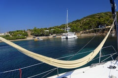 Hammock on a sailing yacht. Hammock on deck of a sailing yacht with view of a catamaran moored in the bay Royalty Free Stock Photo