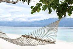 Hammock on sandy beach on background of azure Bali Sea. Coast of the Gili Trawangan island, Indonesia. stock image