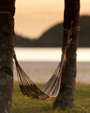 Hammock by sea. Hammock slung between two trees with sea and silhouetted coastline in background stock photography