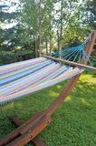 Hammock in the Shade. A colorful garden hammock rests in the shade on a summer evening stock photo