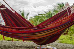 A hammock in the shadow of the palm tree. On the tropical beach - Carate, Costa Rica Stock Image
