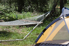 Hammock and tent at campsite. Closeup of hammock and tent in countryside campsite Royalty Free Stock Image