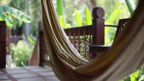 Hammock on the terrace of a villa in the jungle on blurred bokeh from plant. 1920x1080. Hd stock video