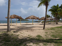Hammock and Tiki Shelters on the Beach Royalty Free Stock Photo