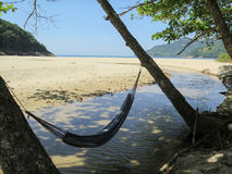 Hammock Time. Hammock by the shade of trees, next to a water stream close to the Martins de Sa beach, near Paraty, Rio de Janeiro, Brazil stock photos