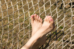 Hammock on trees and female feet with pedicure in spring garden. Hammock on trees and female feet with pedicure in spring garden Royalty Free Stock Images
