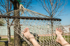 Hammock on trees and female feet with pedicure in spring garden. Stock Photo