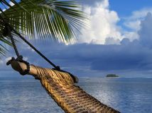 Hammock on tropical beach. Hammock on a palm tree on a tropical beach. Concept of relaxation and vacation Stock Photos