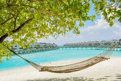 Hammock at the tropical beach with water bungalows at background. At resort Royalty Free Stock Photo