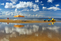 Hammock with an umbrella and chair on the beach with reflection Stock Photography