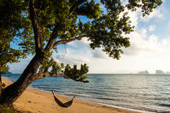 Hammock under leaning tree. Just after sunrise on an island beach in southern Thailand Royalty Free Stock Image