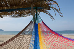 Hammock under a palapa. Colorful hammock end tied under palapa Stock Image