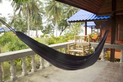 Hammock on veranda. Hammock slung on veranda of Asian home, tropical palm trees in background Royalty Free Stock Image