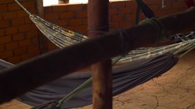 Hammocks under a roof in a southeastern cafe by the road.  stock video