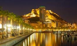 Hamn med yachter mot slott på monteringen i natt Alicante Arkivfoto