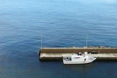 Hamn och liten vit fiskebåt som binds till pir i medelhavet med blått havsvatten på bakgrunden Royaltyfria Bilder