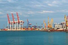 Hamnkranar och olik märkeslast i hamnen Arkivbild