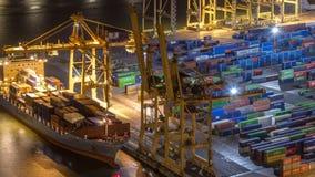 Hamnstad och päfyllningsskeppsdockor på porten med kranar och mång--färgad timelapse för natt för lastbehållare stock video
