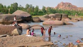 HAMPI, ИНДИЯ - АПРЕЛЬ 2013: Люди купая в реке горы сток-видео