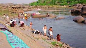 HAMPI, ИНДИЯ - АПРЕЛЬ 2013: Люди купая в реке сток-видео